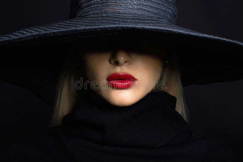 Beautiful woman in hat. Retro fashion.summer hat with large brim. Over dark background stock image