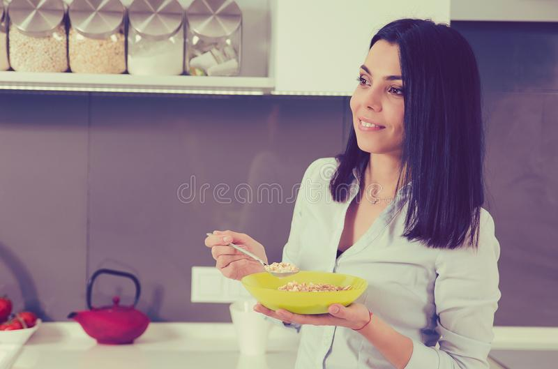Beautiful young woman having breakfast in the kitchen. stock photo