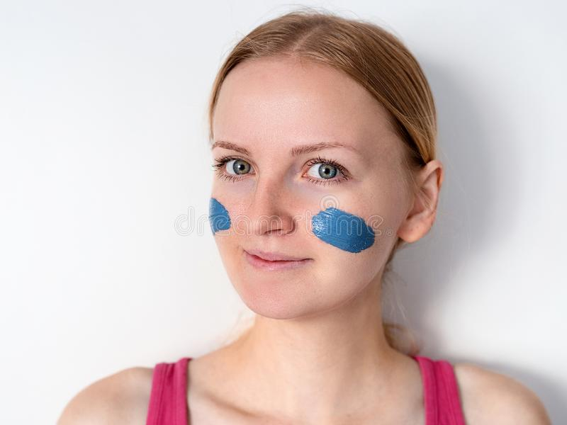 Beautiful blonde woman having blue clay facial mask apply by beautician. girl with a mask on a cheeks is smiling stock images