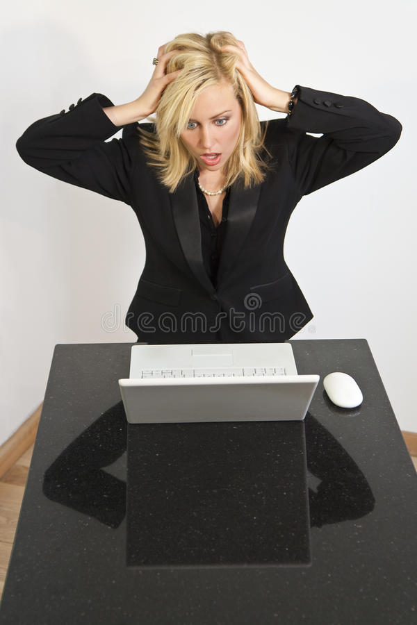Beautiful Woman Having Computer Problems. A stunningly beautiful young woman having problems with her laptop computer royalty free stock photos