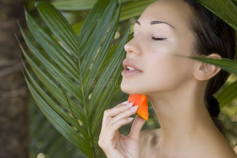 Beautiful woman having fresh papaya facial mask apply. fresh pap. Beautiful caucasian woman having fresh papaya natural facial mask apply, skin care and wellness royalty free stock images