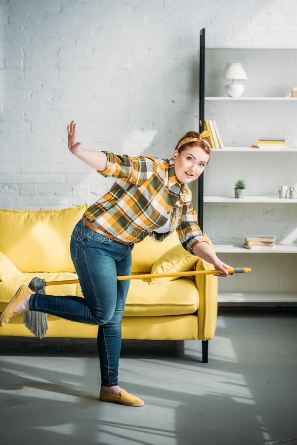 beautiful woman having fun with mop during cleanup royalty free stock image