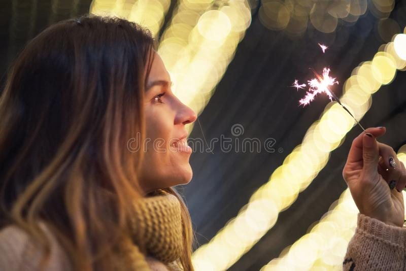 Beautiful woman having fun, with sparkler in her hands celebrating new year eve royalty free stock photography