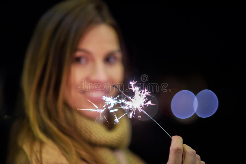 Beautiful woman having fun, with sparkler in her hands celebrating new year eve royalty free stock photo
