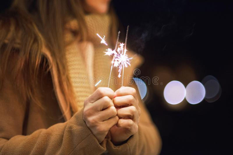 Beautiful woman having fun, with sparkler in her hands celebrating new year eve stock images