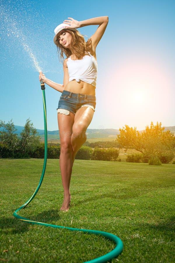 Beautiful woman having fun in summer garden with garden ho stock image
