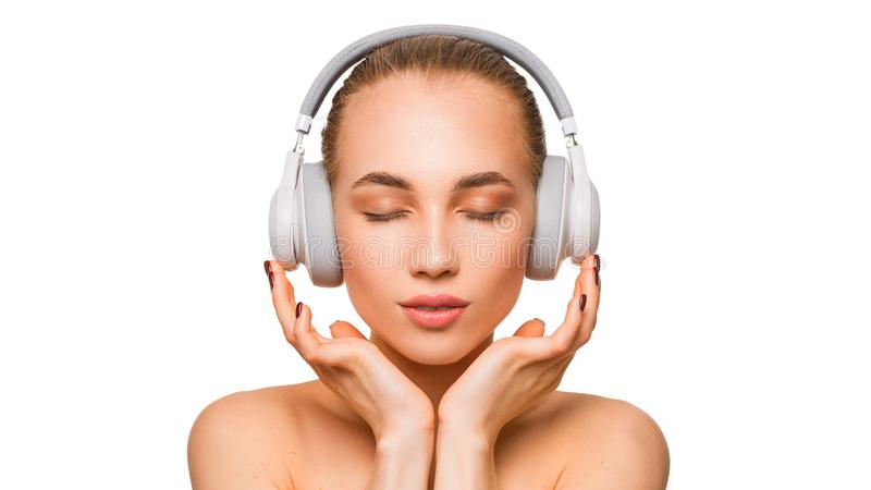 Beautiful woman in headphones listening to the music with closed eyes. stock photography