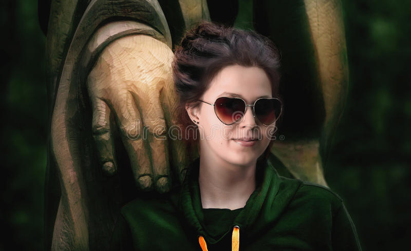 Beautiful woman with heart shaped glasses and a wooden statue stock photography