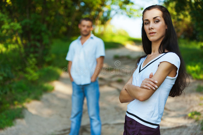 Beautiful woman and her boy friend. Young beautiful women in foreground in summer solar park. Man stands behind in the distance stock image