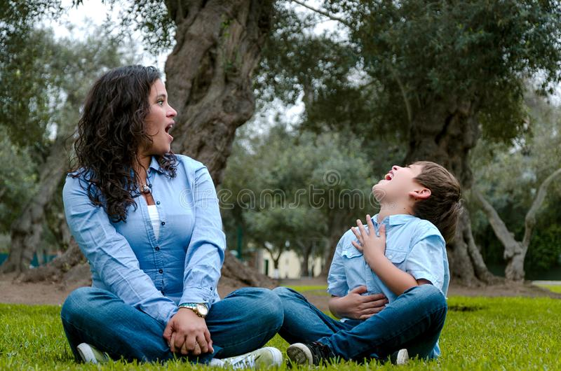 Beautiful woman and her cute little son looking at each other stock photo