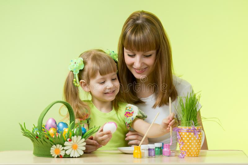 Beautiful woman and her daughter coloring Easter eggs at the table royalty free stock photography
