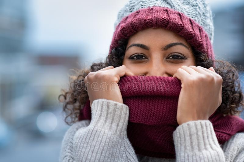Beautiful woman hiding face in woolen scarf. Closeup face of happy african girl holding woolen scarf with hands over nose to protect from the frost. Portrait of royalty free stock photos