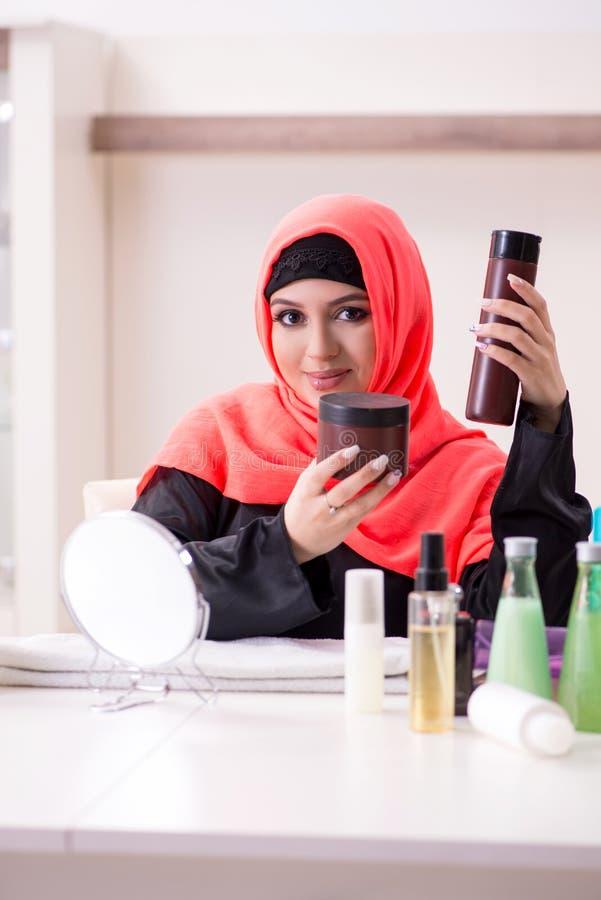 Beautiful woman in hijab applying make-up royalty free stock photo