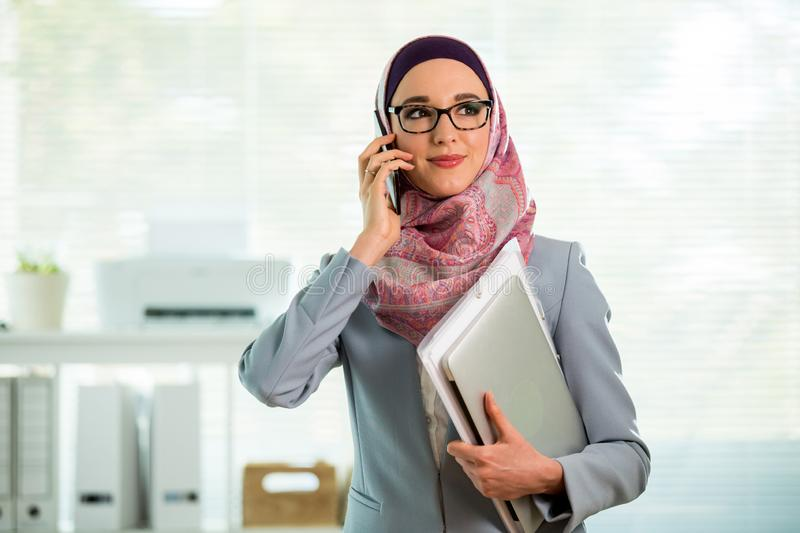 Beautiful woman in hijab and eyeglasses talking on phone royalty free stock photo
