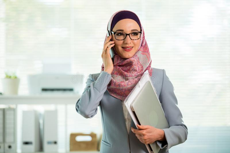 Beautiful woman in hijab and eyeglasses talking on phone stock images