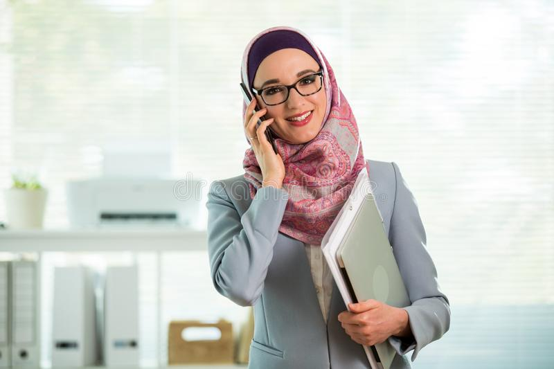 Beautiful woman in hijab and eyeglasses talking on phone stock photo