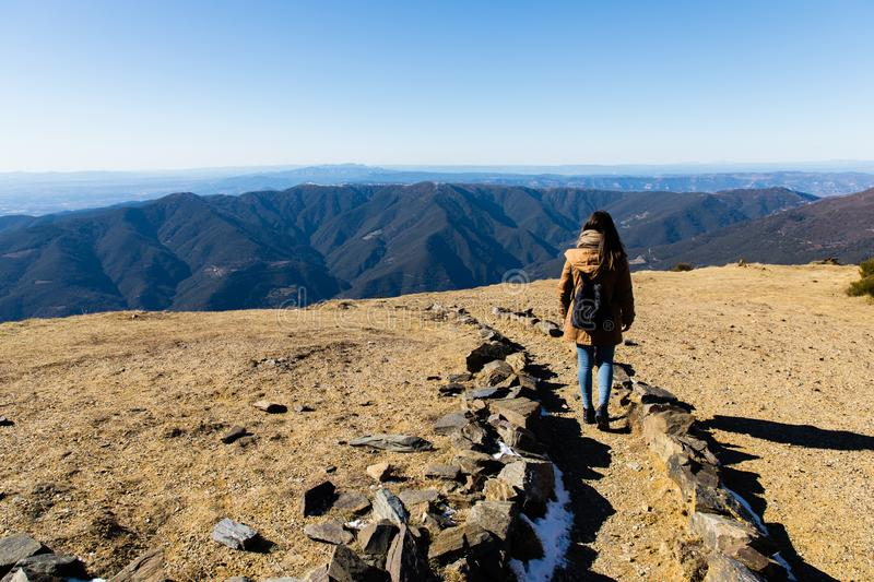 Beautiful woman hiking on mountain path during winter or autumn in Catalonia & x28;Turo del Home - Spain. & x29; with copy space, landscape, alpine, extreme royalty free stock photo