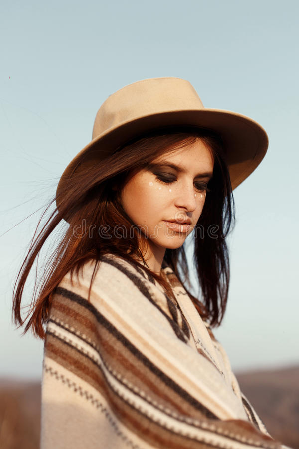 Beautiful woman hipster portrait, with romantic look, wearing hat and poncho at sunset in mountains, boho travel concept. Beautiful woman hipster portrait, with royalty free stock image