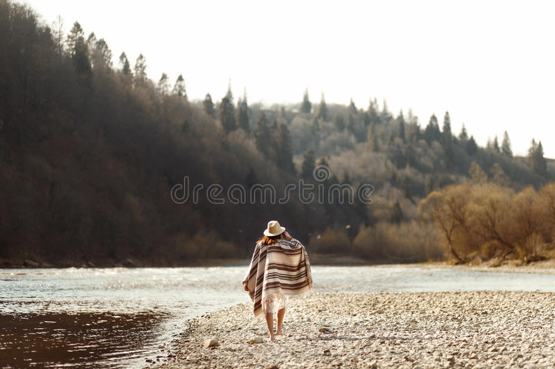 Beautiful woman hipster walking on river beach in mountains, wear. Ing hat and poncho, boho travel concept, space for text royalty free stock photo