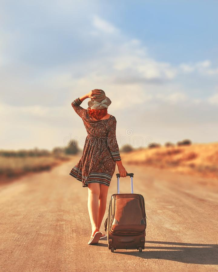 Beautiful woman hitchhiking. Cute woman in summer dress and hat hitchhiking with suitcase at autumn toned. Female walking on the road with Luggage. Freedom stock image