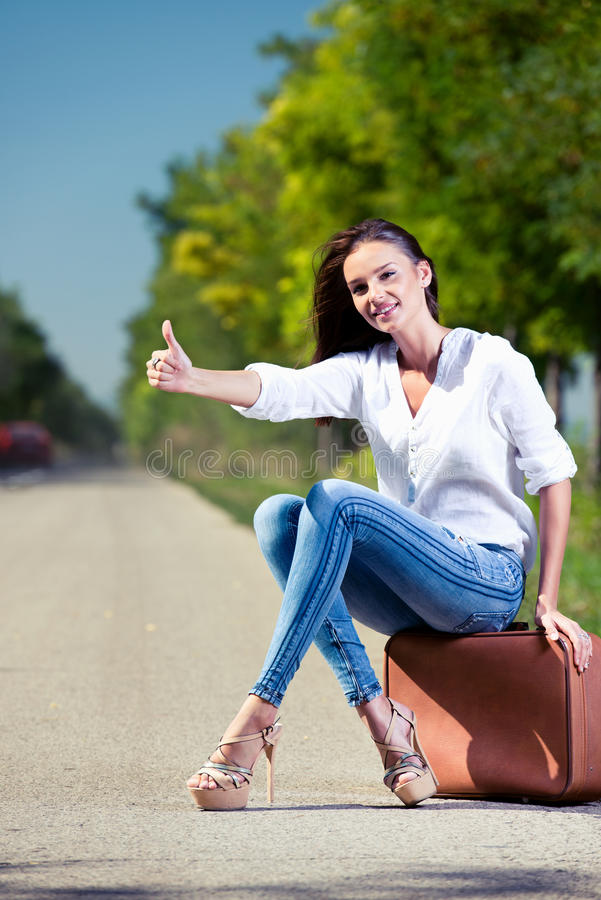 Beautiful woman hitchhiking. With suitcase stock photos
