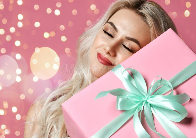 Beautiful woman hold pink Christmas presents gift box for new year celebration smiling dreaming. On pink background with bokeh lights stock photos