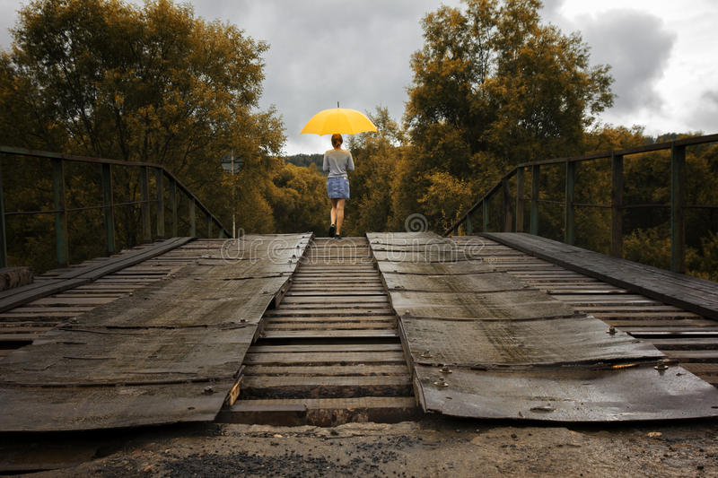 Beautiful woman hold yellow umbrella and walking on a old bridge in the countryside under rain.  royalty free stock image