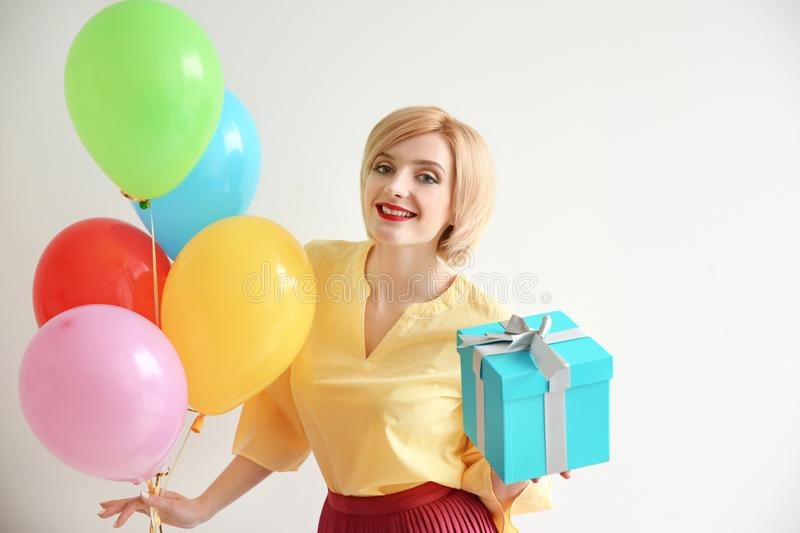 Beautiful woman holding air balloons and gift box stock images