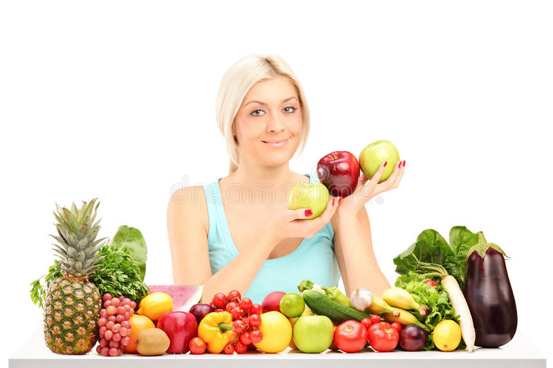 Beautiful woman holding apples behind a table full of fruits. Beautiful young woman holding apples behind a table full of fruits and vegetables on white stock image