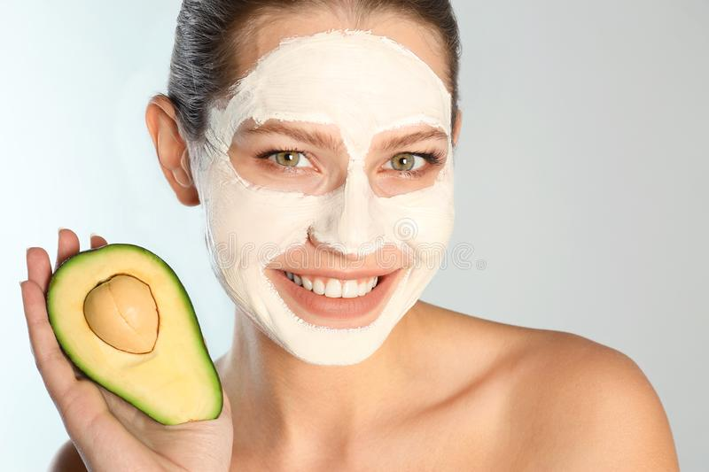 Beautiful woman holding avocado near her face with clay mask against grey background. Closeup stock photography