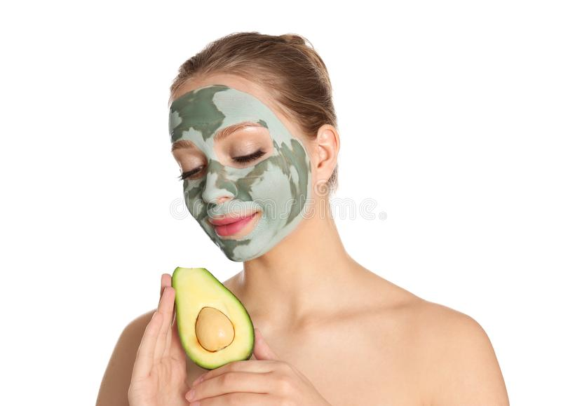 Beautiful woman holding avocado near her face with clay mask. On white background royalty free stock image