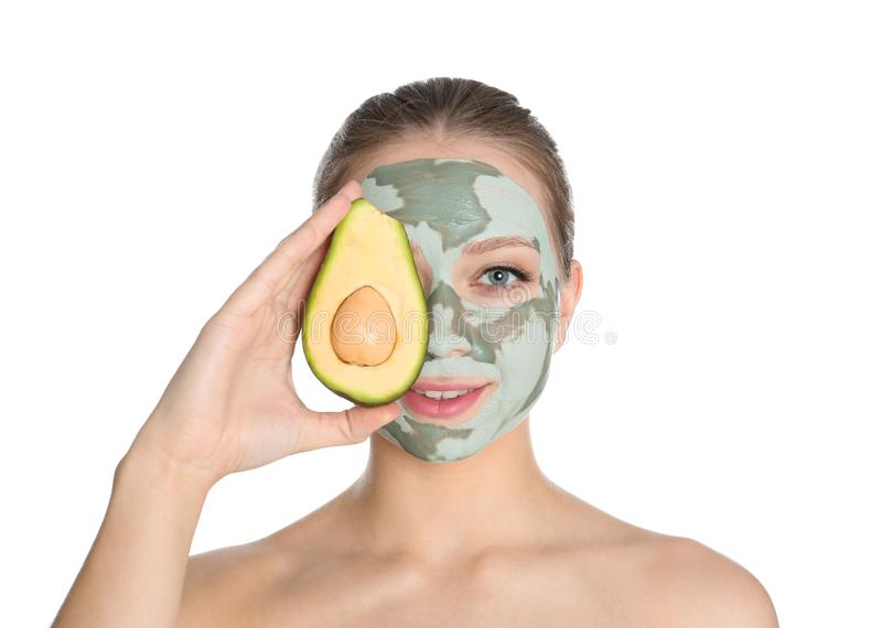 Beautiful woman holding avocado near her face with clay mask on white. Background stock photography