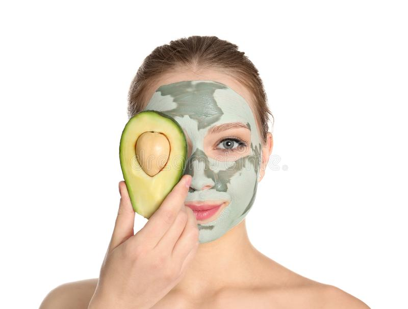 Beautiful woman holding avocado near her face with mask. Beautiful woman holding avocado near her face with clay mask on white background stock photo