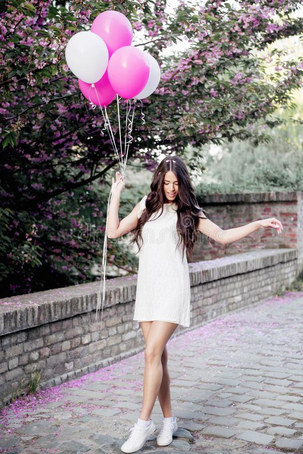 Beautiful woman holding balloons outdoors royalty free stock photo