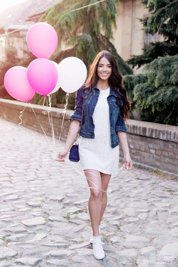 Beautiful woman holding balloons outdoors royalty free stock images