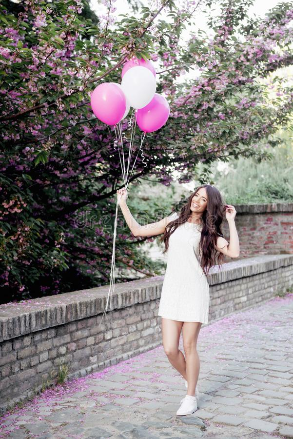 Beautiful woman holding balloons outdoors stock photo