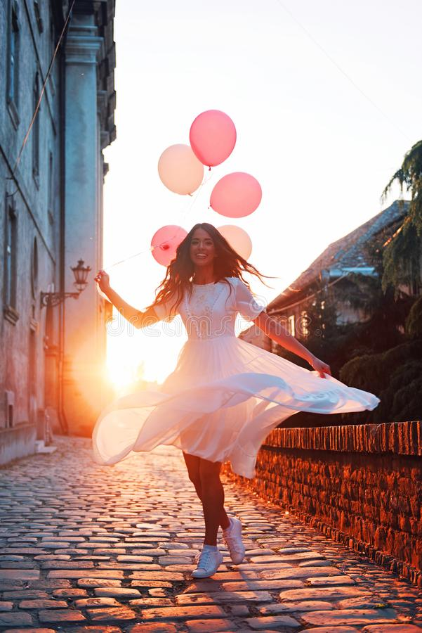 Beautiful woman holding balloons outdoors stock photography