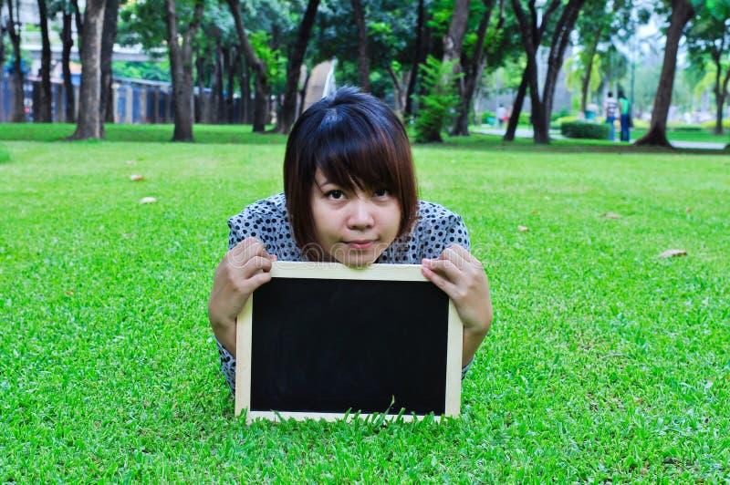 Beautiful woman holding blackboard in the park stock photos
