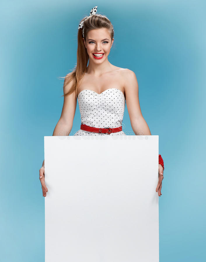 Beautiful woman holding a blank billboard on blue background royalty free stock photos