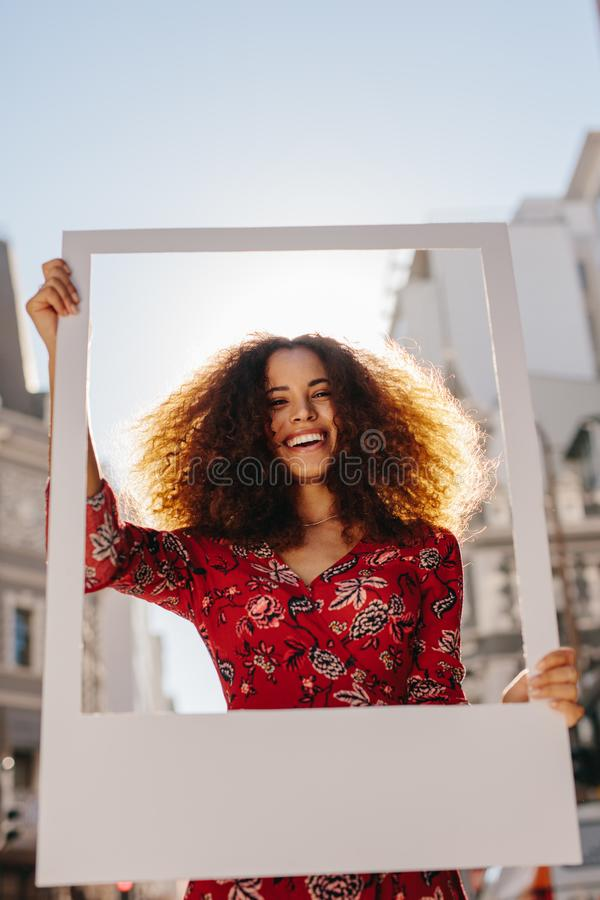 Beautiful woman holding a blank photo frame royalty free stock photos