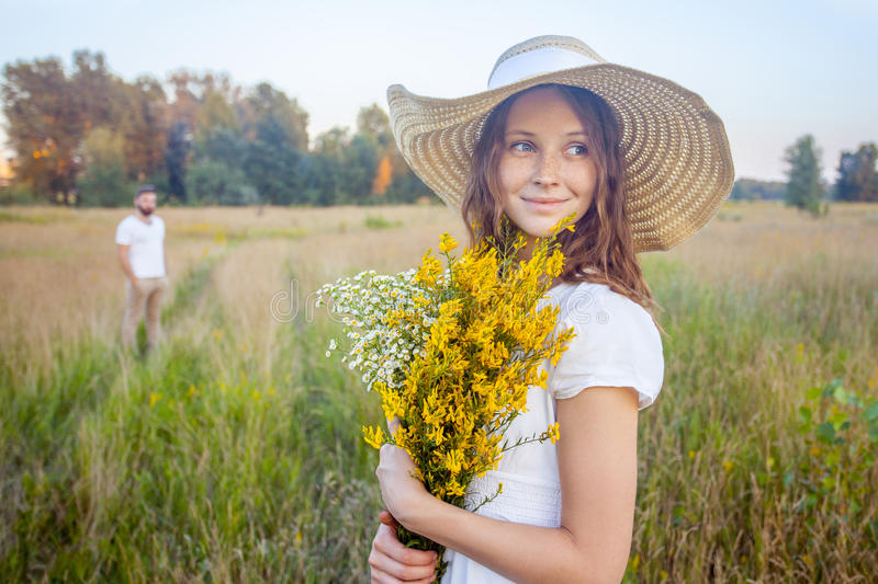Beautiful woman holding bouquet of yellow flowers and looking at camera with her boyfriend on background. stock image