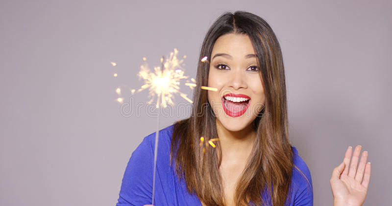 Beautiful woman holding a burning sparkler. Beautiful woman in a stylish blue top holding a burning sparkler to celebrate the festive season over a grey royalty free stock photos