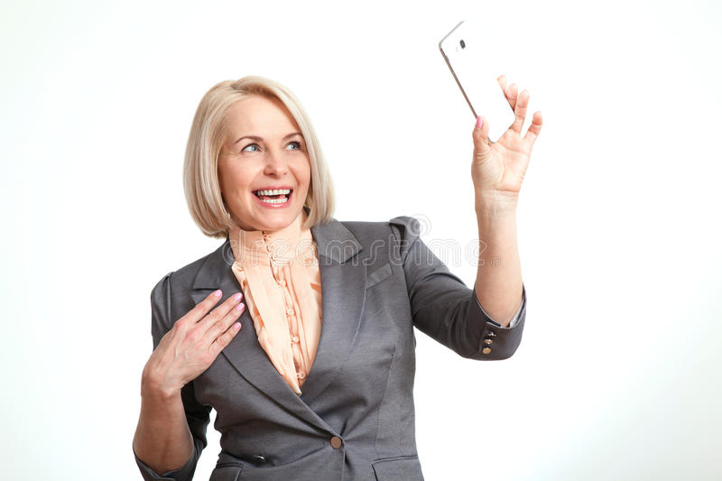 Beautiful woman holding camera and making selfie. royalty free stock photography