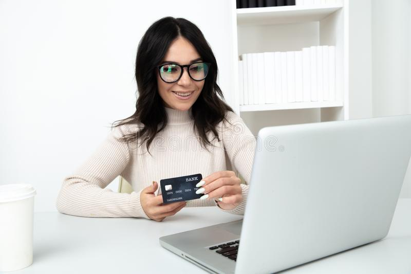 Beautiful woman holding card and using notebook to make online shopping. stock image