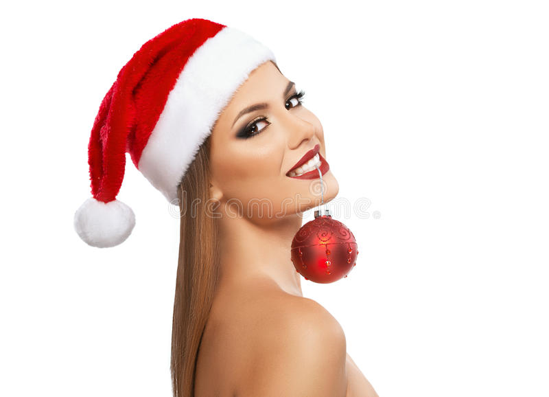 Beautiful woman holding a Christmas ornament with teeth, close-up over white background stock photos