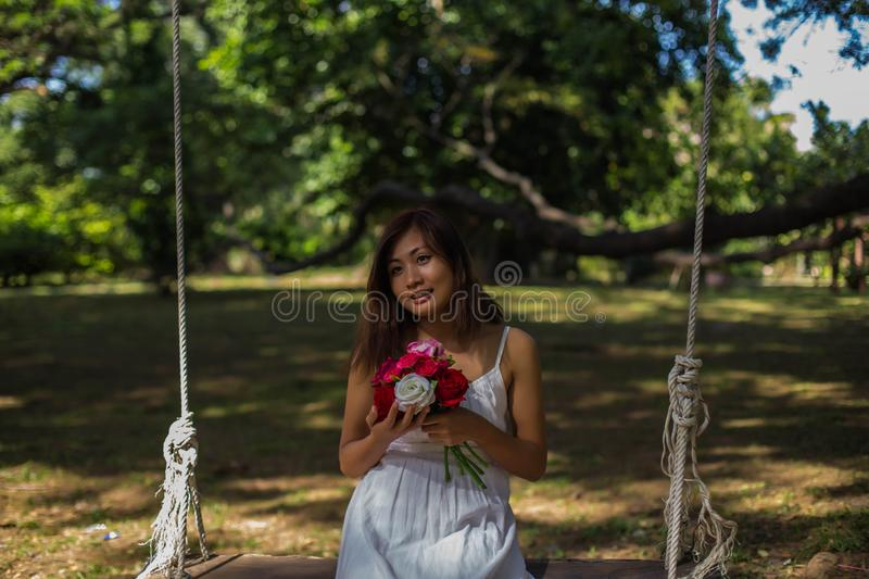 Beautiful women holding flowers, swinging under the trees stock photography
