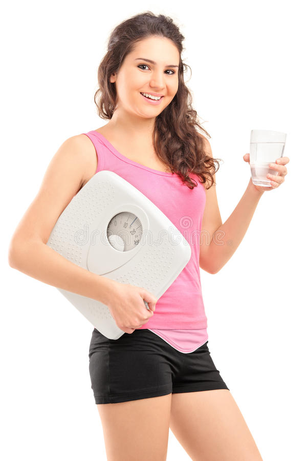 Beautiful woman holding glass of water and weight scale royalty free stock photos