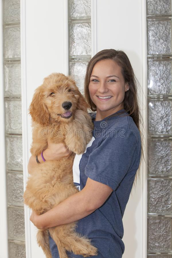 Beautiful Woman Holding Goldendoodle Puppy stock photography