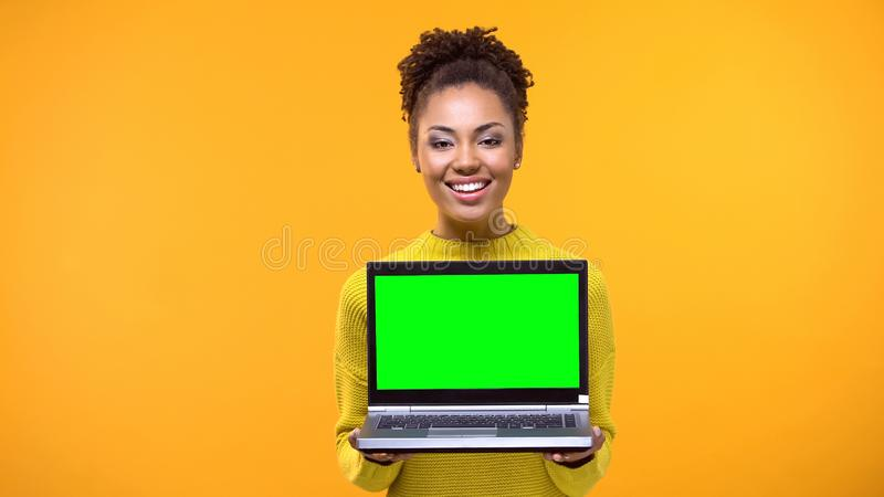Beautiful woman holding green screen laptop, shopping online, bookmakers office. Stock photo royalty free stock photo