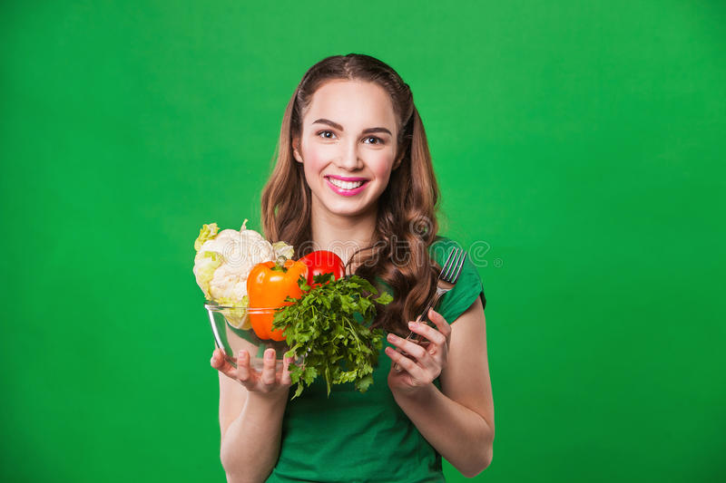 Beautiful woman holding a grocery bag full of. Young woman holding a bag full of healthy food. on green background. shopping royalty free stock photos